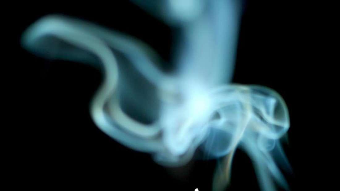 Man sieht eine Zigarette und Zigaretten-Qualm (Symbolbild).