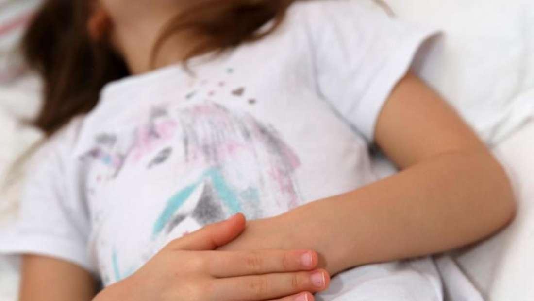 Ein Kind fasst sich im Liegen an den Unterbauch (Symbolbild).