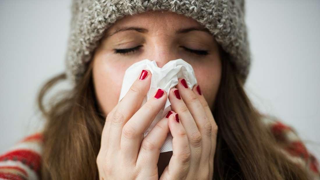 Eine Frau mit Mütze putzt sich die Nase (Symbolfoto).