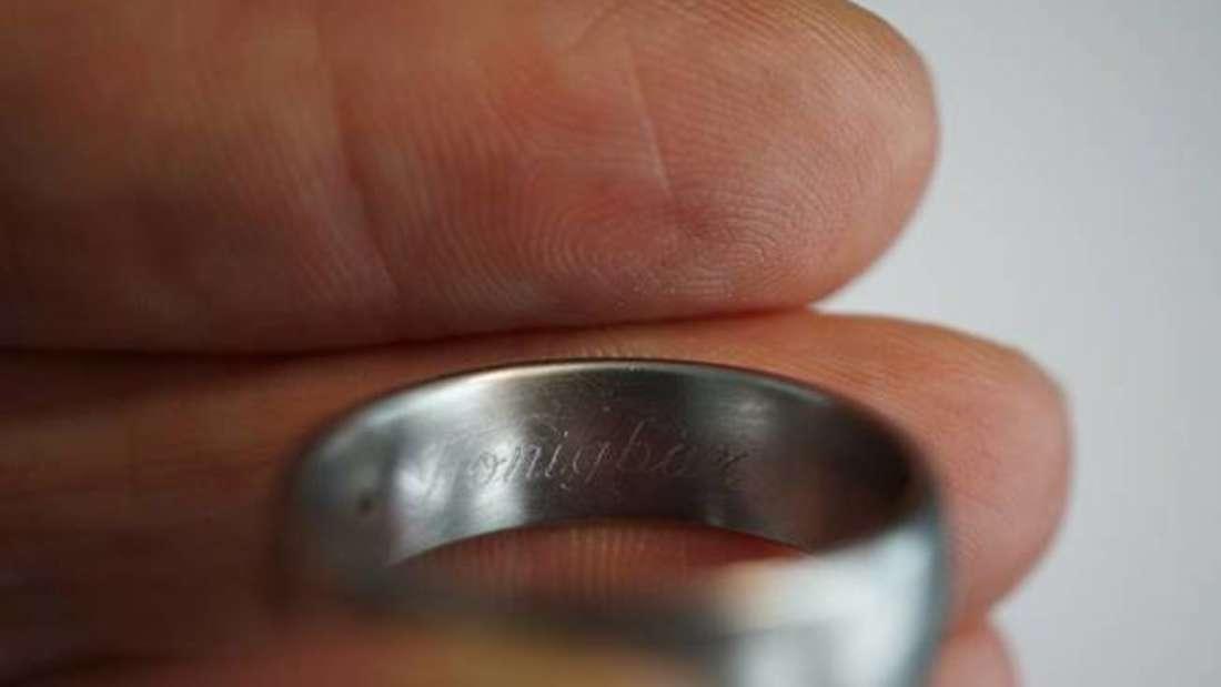 Jemand hält einen Ring mit Gravur in der Hand.