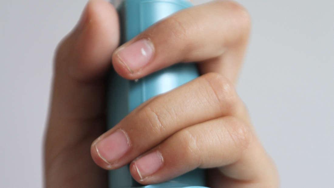 Eine Frau hält ein Asthma-Spray (Inhalator) in der Hand.
