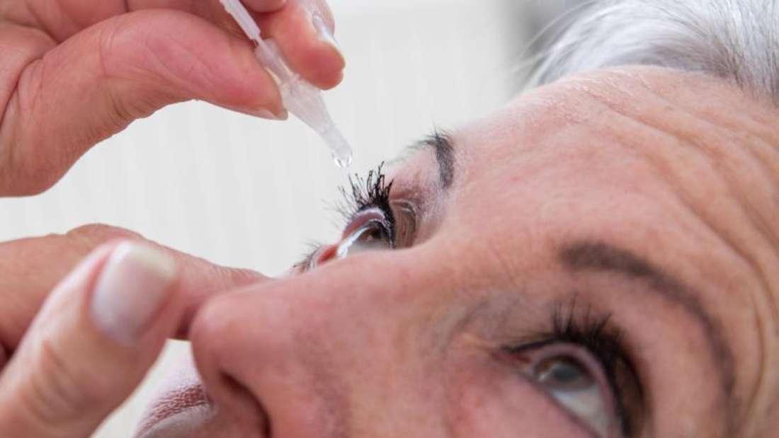 Eine Frau tropft sich Augentropfen in die Augen (Symbolbild).