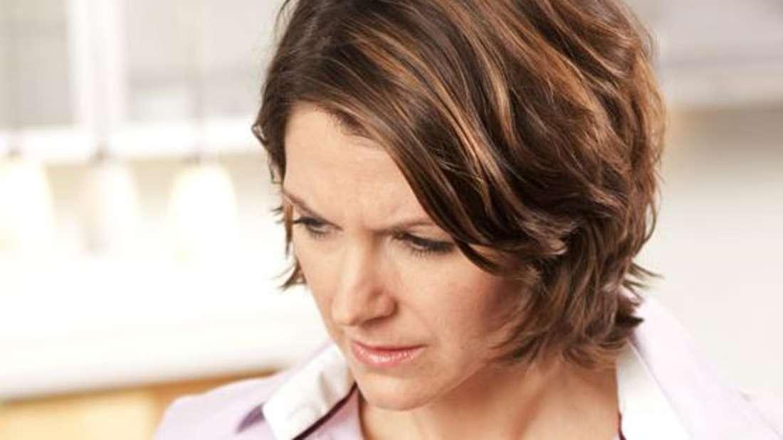 Eine Frau fasst sich mit schmerzverzerrtem Gesicht an den Hals, wo die Speiseröhre liegt (Symbolbild).
