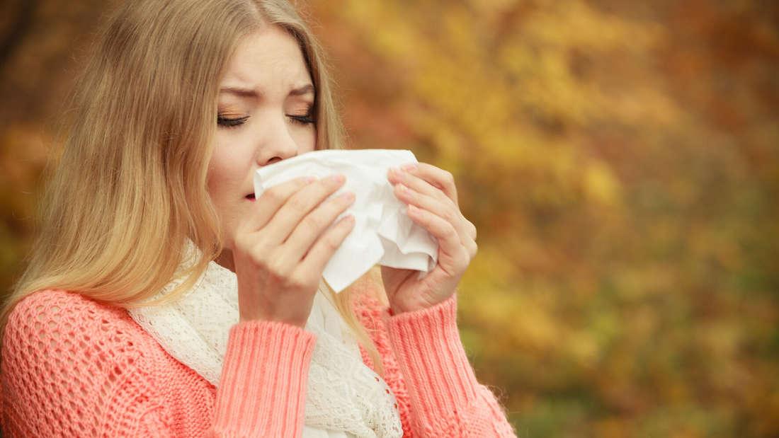 Eine Frau in lachsfarbenem Pullover niest in ein Taschentuch (Symbolbild).