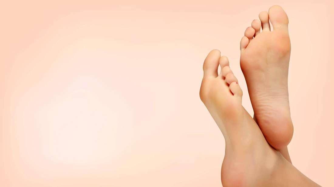 Eine Frau streckt ihre Füße vor einem rosefarbenen Hintergrund in die Höhe (Symbolbild).