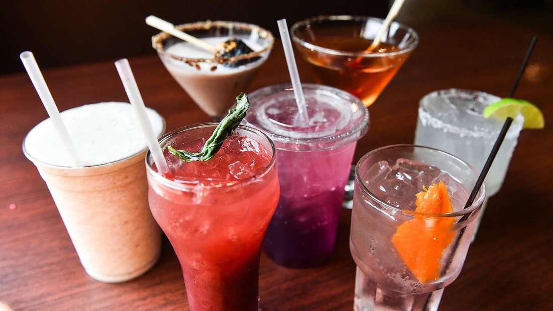 Milchmixgetränke, Eistees und Cocktails stehen in Plastikbechern und Gläsern auf einem Holztisch (Symbolbild).
