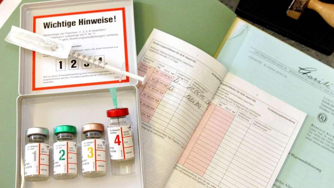 Medikamente in Glasfläschchen für eine spezifische Immuntherapie und eine Spritze liegen auf medizinischen Unterlagen (Symbolbild).