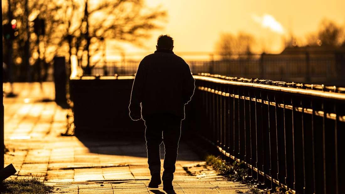 Ein älterer Herr geht dem Sonnenuntergang entgegen, er ist allein (Symbolfoto)