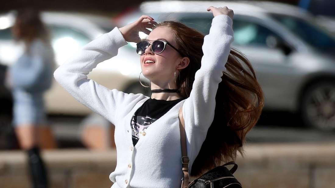 Ein Mädchen dreht den Kopf zum Himmel, lacht und hat eine Sonnenbrille auf (Symbolfoto).