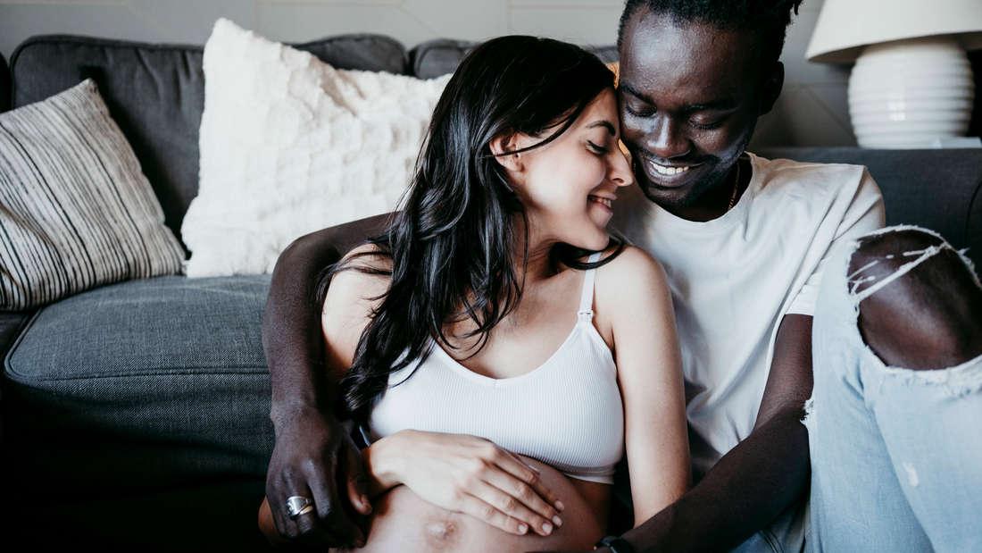 Ein Mann, der seine schwangere Frau festhält. Beide sehen sehr glücklich aus (Symbolbild)