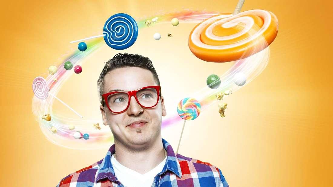 Mann vor gelbem Hintergrund; trägt rote Brille; um seinen Kopf kreisen Süßigkeiten (Symbolbild)