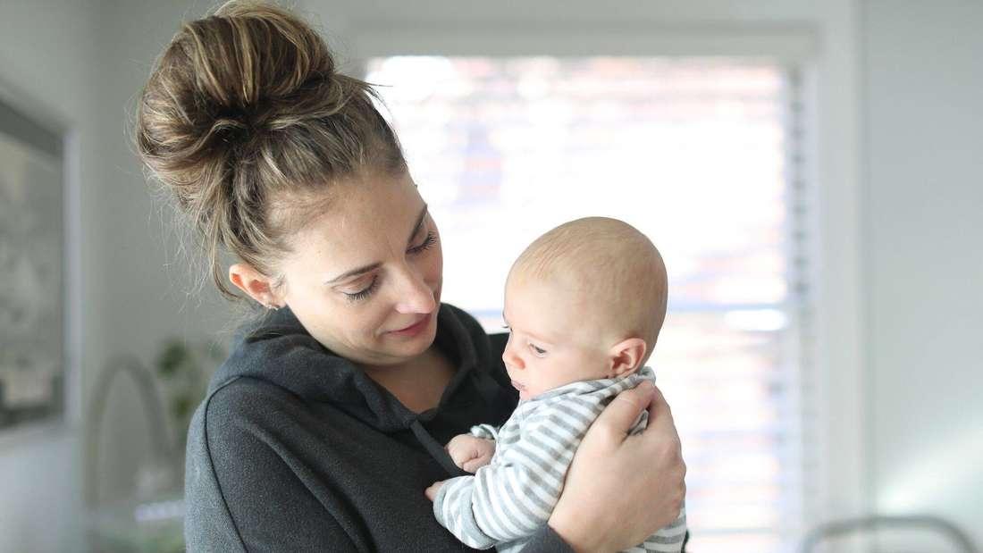 Junge Frau mit Dutt trägt ein Neugeborenes auf dem Arm (Symbolbild)