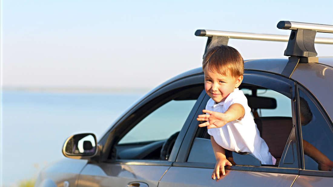 Ein Junge winkt aus einem grauen Auto. (Symbolbild)