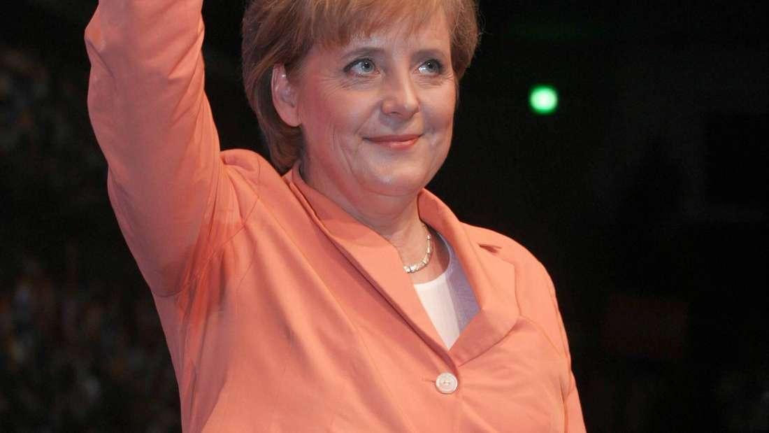 Angela Merkel winkt und hat einen Schweißfleck unter dem Arm. (Symbolbild)