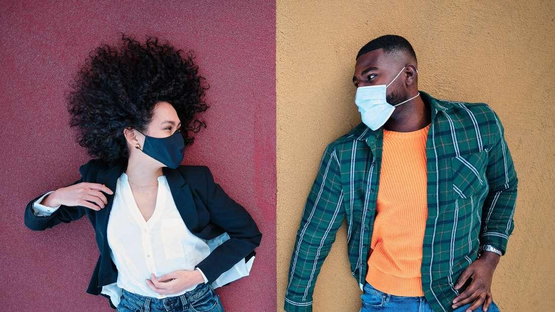 Eine Frau und ein Mann mit Corona-Masken im Gesicht liegen auf dem Boden und sehen sich an (Symbolbild)