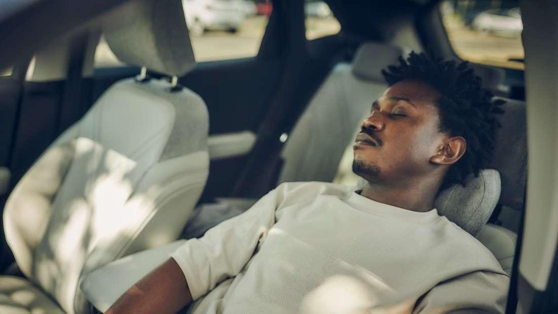 Ein junger Mann sitzt auf dem Fahrersitz eines Autos und schläft.