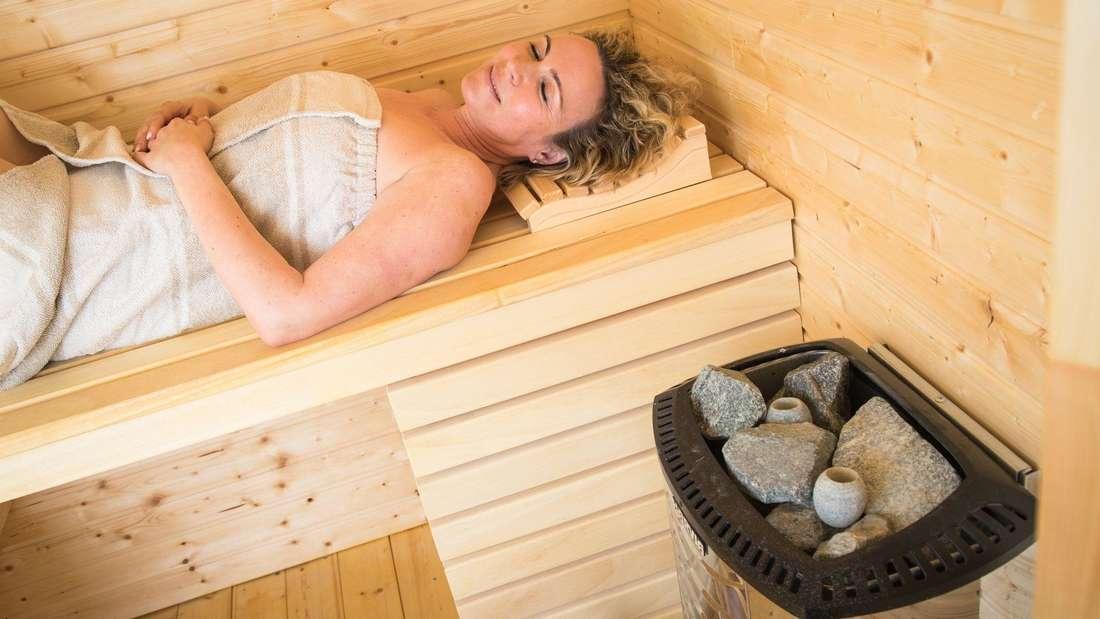 Eine Frau liegt in einer Sauna und entspannt. (Symbolbild)