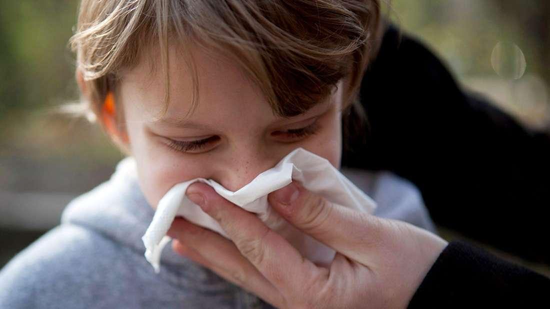 Ein Kind schnäuzt sich mithilfe eines Erwachsenen in ein Taschentuch.