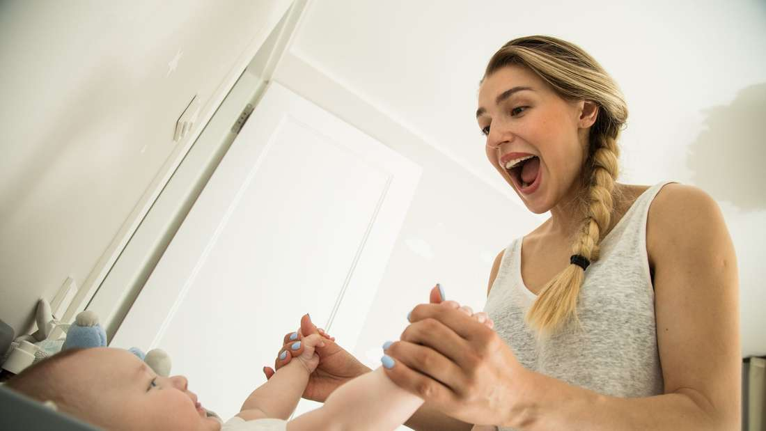 Eine junge Mutter macht mit ihrem Baby Faxen. (Symbolbild)
